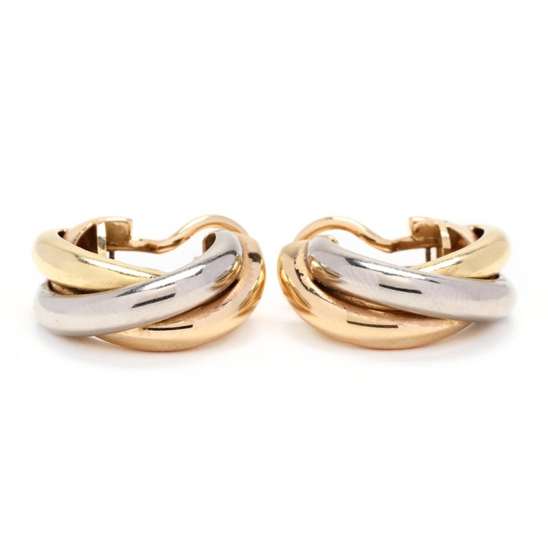 18k yellow, white and rose gold Cartier hoop earrings. Classic tricolor hoops that twist by the famous jewelry house Cartier. As a shrimp style they have a post and leverback for easy on and off and security. A timeless addition to any