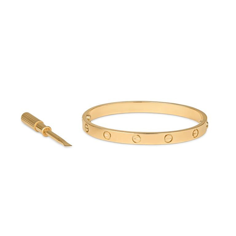 This classic 18kt Yellow Gold Cartier Love Bracelet features the new style screw system with the original Cartier screwdriver. Size 18. MSRP $6,300. It is in good condition and has been professionally polished and has only minor signs of wear that