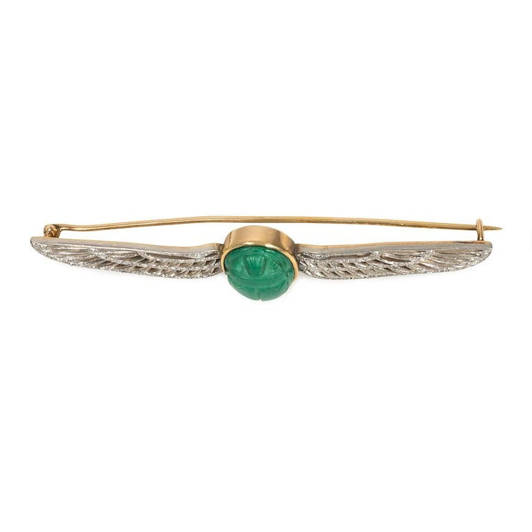 An Edwardian brooch in the Egyptian Revival style comprised of a faience scarab flanked by openwork diamond wings, in 14k gold and platinum. Cartier #0274