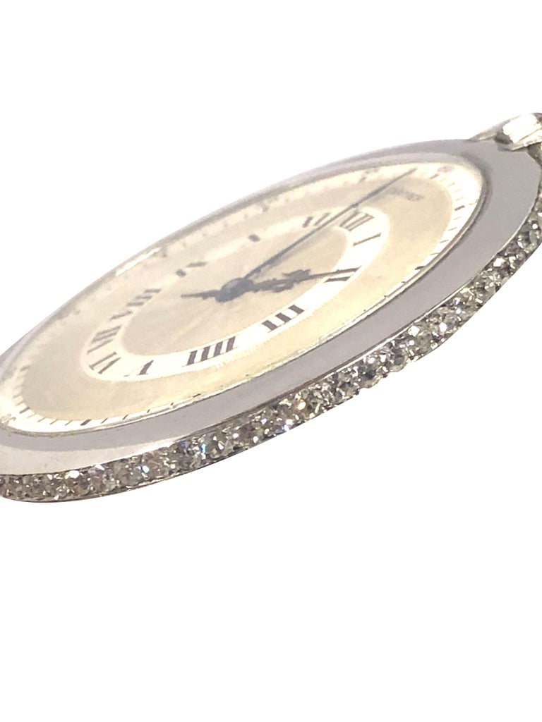 Circa 1920s Cartier Pocket Watch, 45 M.M. Platinum 3 Piece case with Diamond set case perimeter, approximately 2 Carats. Jeweled Nickel lever mechanical wind movement by EWC, European Watch & Clock. original Silver Satin Engine turned dial with