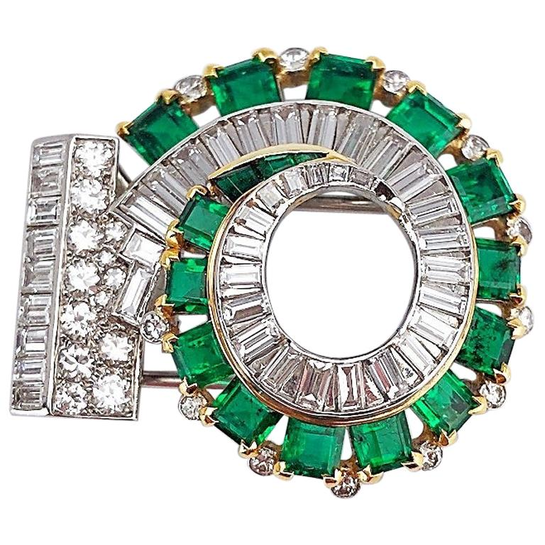Circa 1930's. Platinum and 18 karat yellow gold swirl brooch set with approximately 3.50 carats of round and baguette cut diamonds, and approximately 6.53 carats of  square emerald cut emeralds. Double clip brooch  1.5
