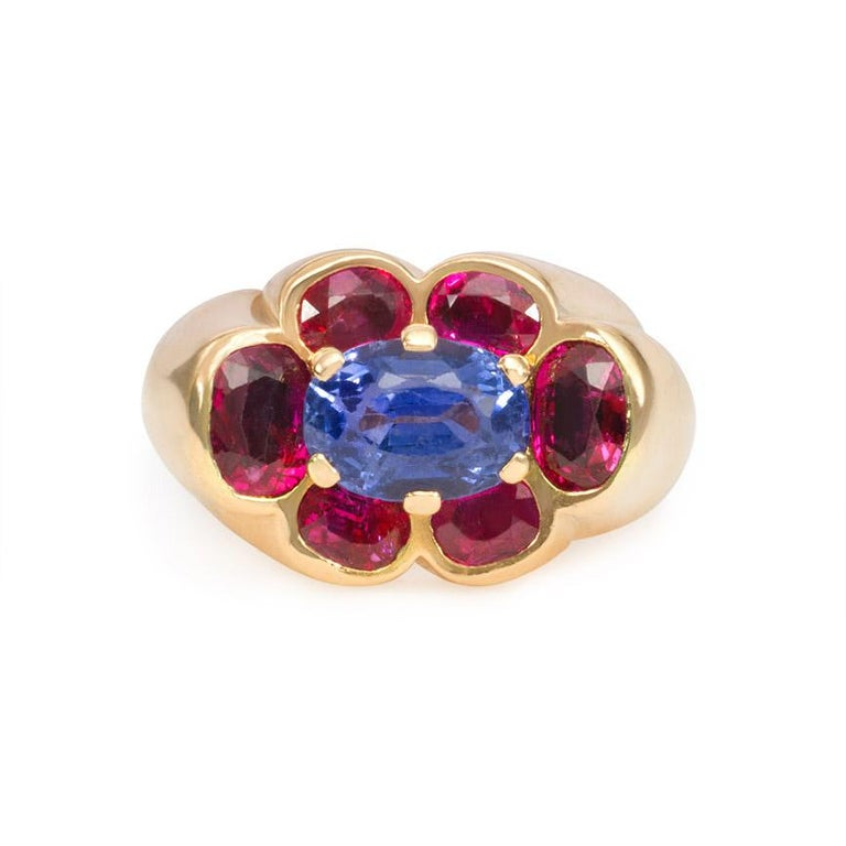 A Retro gold ring of fluted design centering on an inset stylized florette of pink and blue sapphires, in 18k. Cartier, Paris #05472.  Atw center sapphire 3.98 cts.  Florette measures approximately 9/16
