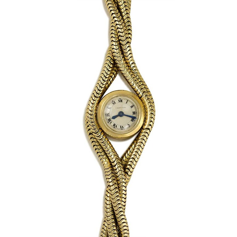 A Retro gold backwinder wrist watch comprised of a bracelet of four twisted snakechains and a circular face with Roman numerals, in 18k.  Cartier, Paris, no. 86743.  Diameter of face measures approximately 0.5 inch.