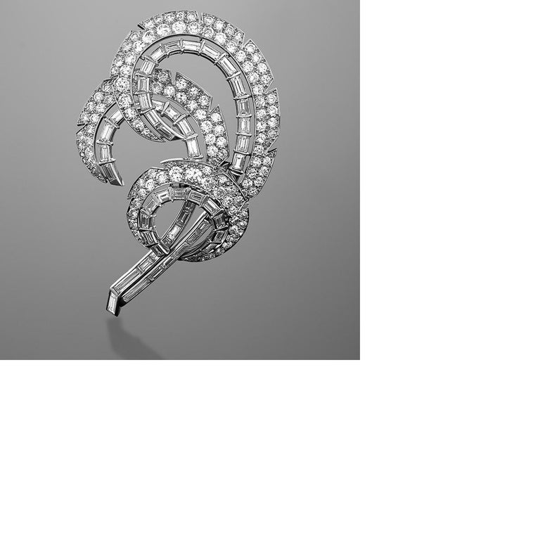 A Mid-20th Century platinum brooch with diamonds in a stylized double feather motif by Cartier. The brooch features 132 round-cut diamonds with an approximate total weight of 5.00 carats, and 48 baguette diamonds with an approximate total weight of