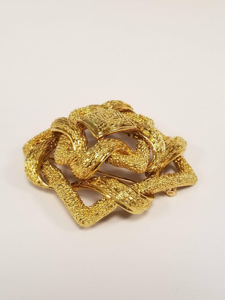 An 18 karat yellow gold brooch with a woven knot design signed Cartier. The heavily textured brooch is designed in a dimensional open-work woven square motif centering on a textured square plaque. Circa 1960's.  Signed,