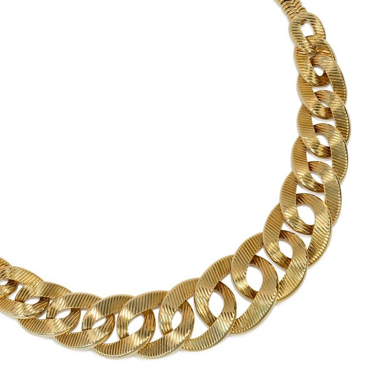 A gold necklace of graduating ribbed curb links with a back chain of chevron-shaped tubular links, in 18k.  Cartier, Paris.  In superb condition with wonderful heft  Dimensions: Approximately 15