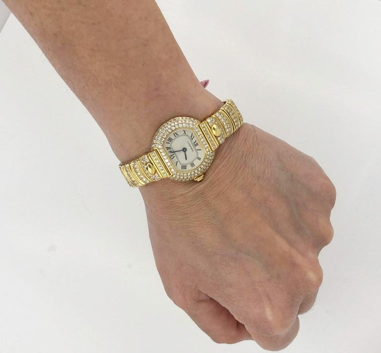 CARTIER 26mm Diamond Watch in 18k Yellow Gold.  A classic watch by Cartier with an east west look – featuring a white sheen face surrounded by rows of white diamond pave mounted in 18k yellow gold.  Diamond weight approx. 5.00 carats total. Approx.