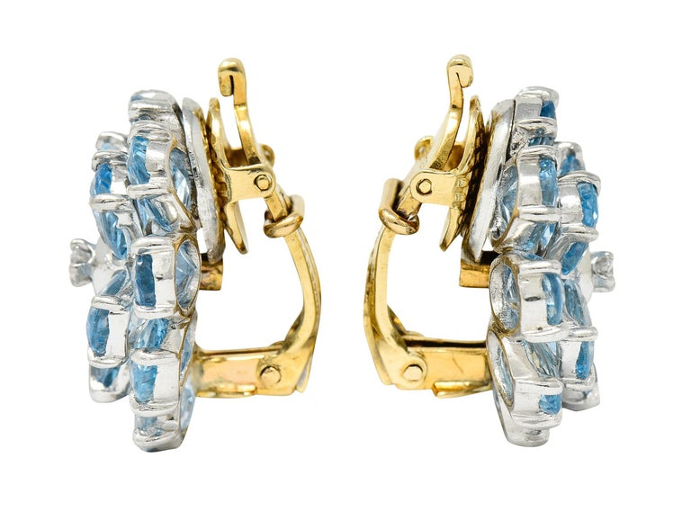 Earrings are designed as flowers with undulating and radiating petals  Petals are oval cut aquamarines weighing in total approximately 28.50 carats  Transparent and a very well matched light sky blue color  Centering round brilliant cut diamonds