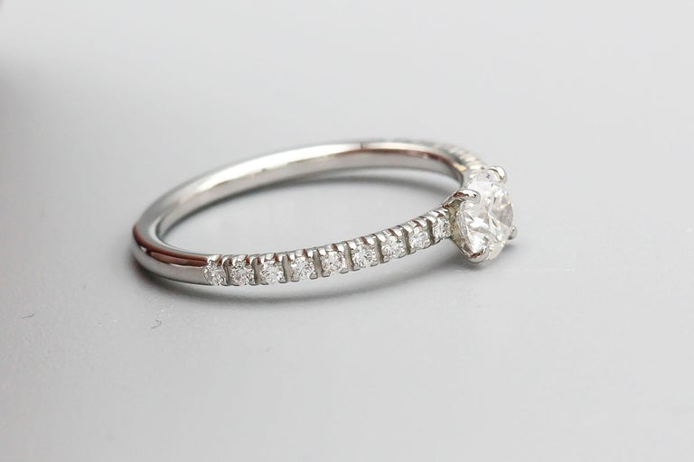 Classic diamond and platinum engagement ring by Cartier. It features high grade round brilliant cut diamonds throughout the sides with a .30ct central stone, E color, VS1 clarity,  as stated in the GIA diamond certificate. European size 46. Includes