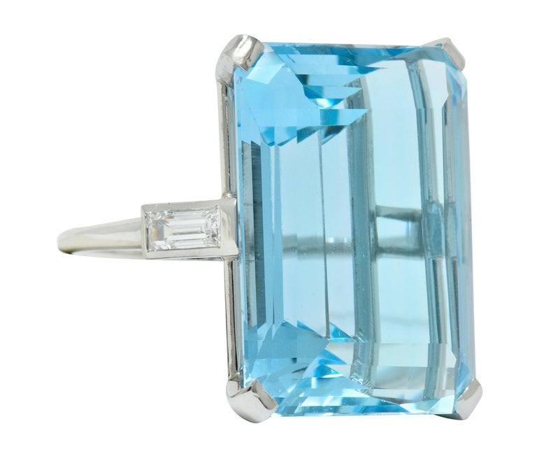 Designed as a cathedral basket style ring centering an emerald cut aquamarine weighing approximately 35.49 carats, transparent and a striking light blue color  Flanked by two baguette cut diamonds, flush set into shoulders, weighing approximately