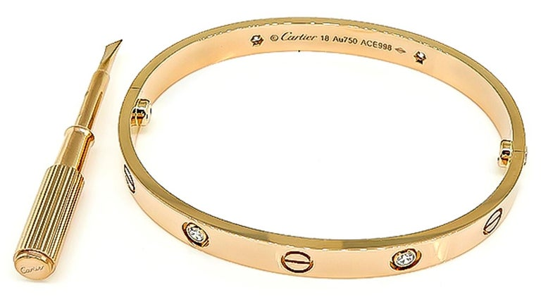 This elegant 18k pink gold love bangle by Cartier is set with 4 sparkling round cut diamonds that weigh approximately 0.40ct. The bangle measures 6mm in width. It is size 18 and weighs 31.7 grams. The bangle is signed Cartier 18 Au750 ACE998 and it