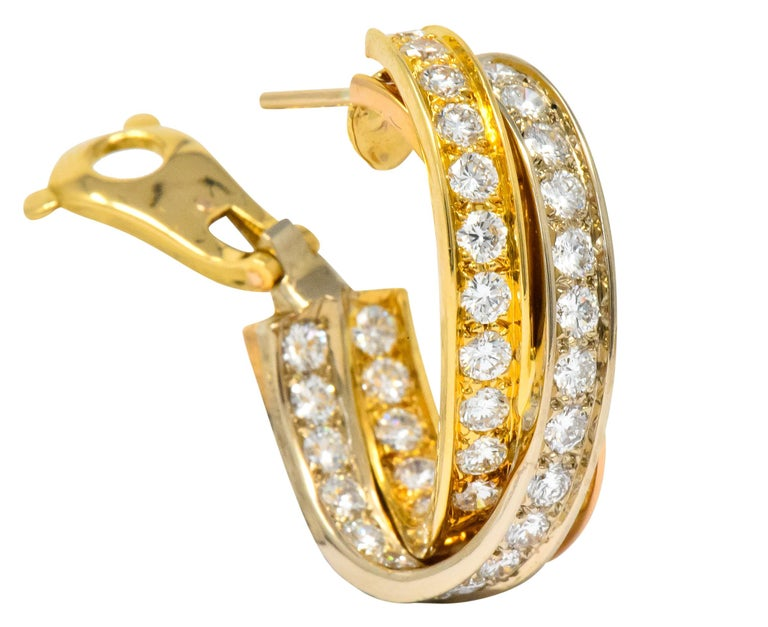 Half hoop design incorporating yellow gold, rose gold, and white gold intertwining channels  Each bead set with round brilliant cut diamonds weighing approximately 5.00 carats total, E/F color and VVS to VS clarity  From Cartier Trinity