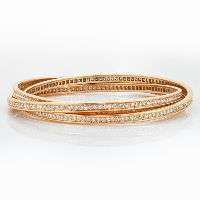 Cartier 18k yellow gold and diamond trinity rolling bangle bracelet with French hallmarks and Cartier box.   This Cartier trinity bracelet is made up of 3 intertwining bangles set all the way around with round brilliant cut diamonds totaling