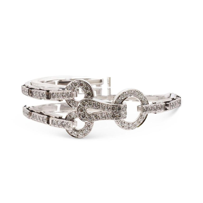 Authentic Cartier Agrafe bracelet comprised of brickwork links and completed with hook and eye closure. Both the clasp and links are set with a total of approximately 4 carats of round brilliant cut diamonds (F-G color, VS clarity). Signed Cartier,