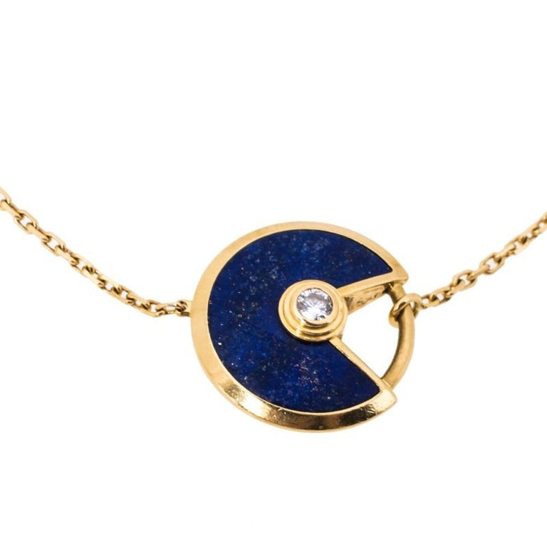 A magnificent offering from Cartier's Amulette de Cartier line. The bracelet comes sculpted from 18k yellow gold and it has the signature motif in Lapis Lazuli highlighted by a shimmering diamond. Smoothly finished, the desirable creation deserves