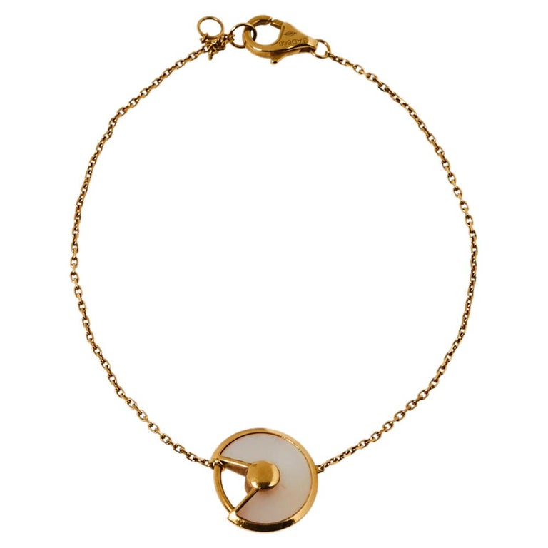 A magnificent offering from Cartier's Amulette de Cartier line. The bracelet comes sculpted from 18k yellow gold and it has the signature motif in a mother of pearl highlighted by a shimmering diamond. Smoothly finished, the desirable creation