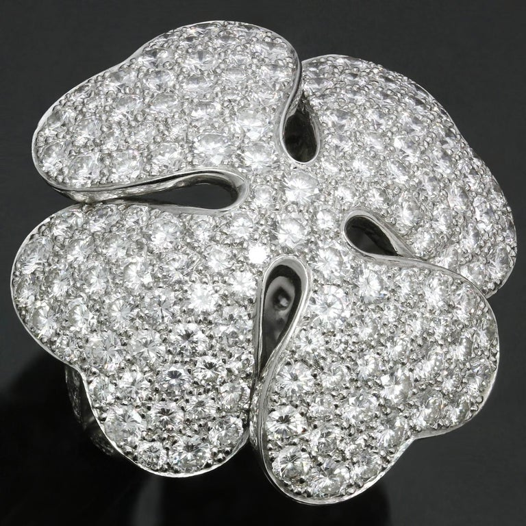 This magnificent ring from Cartier's Anniversary edition features a sparkling floral clover design pave-set with brilliant-cut round diamonds of an estimated 10.0 carats in 18k white gold. Made in France circa 2001. Completed with original Cartier
