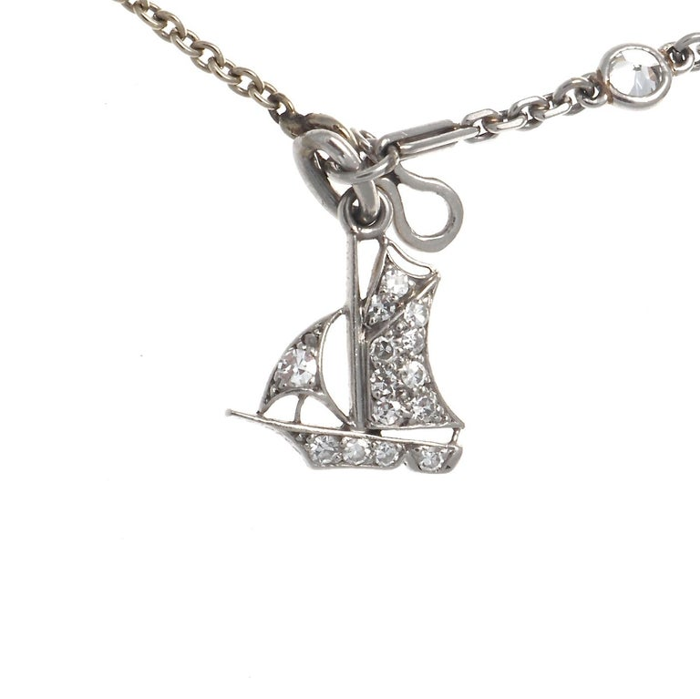 Art Deco bracelet. Featuring a diamond heart charm that has 16 diamonds signed Cartier London. A doghouse charm with 9 diamonds  and 1 sapphire, signed J. Lacloche. A sailboat charm with 15 diamonds signed Cartier London serial #3466. A dog charm