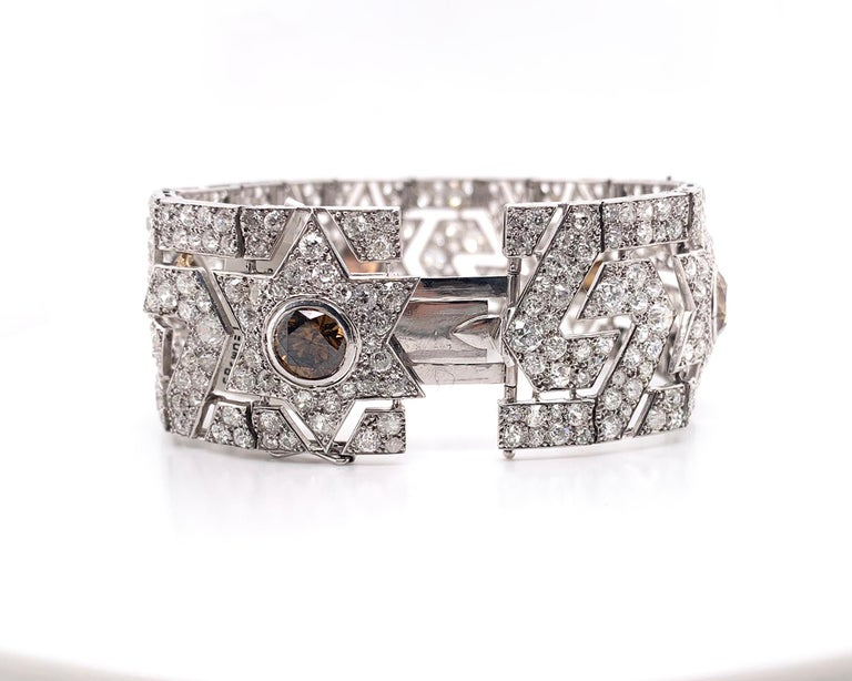 A stunning Art Deco bracelet embellished with 5 brown diamonds weighing 11.00 carats total and white diamonds weighing 16.00 carats total.  The length is 7 inches (17.7 cm). Weight of platinum is 55.00 grams. Signed Cartier Paris Londres New