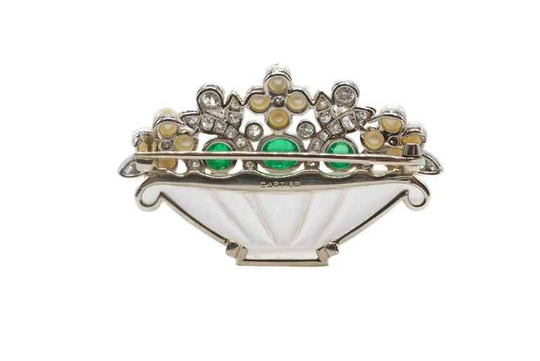 Unique and rare Art-Deco brooch by Cartier designed as a bouquet of flowers in a crystal vase. A finely carved piece of opaque rock crystal is the base for a beautiful bouquet designed out of bright white and sparkly old cut round diamonds set in