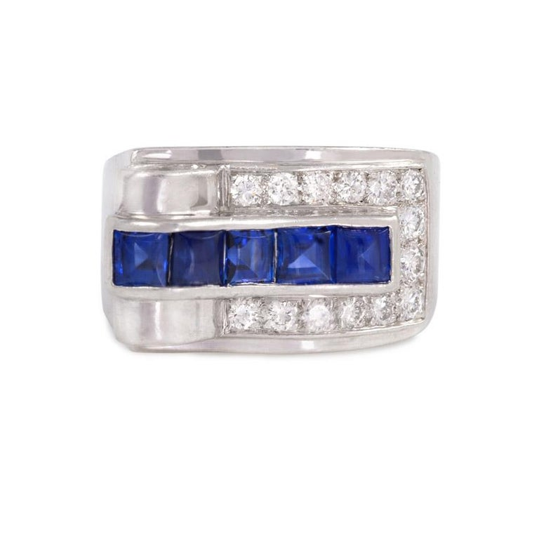 An Art Deco diamond and buff-top sapphire ring of asymmetrical geometric design, featuring an open loop on one end and a triangular diamond in the shoulder, in platinum. Cartier  Top measures approximately 1.9cm across, 11mm wide