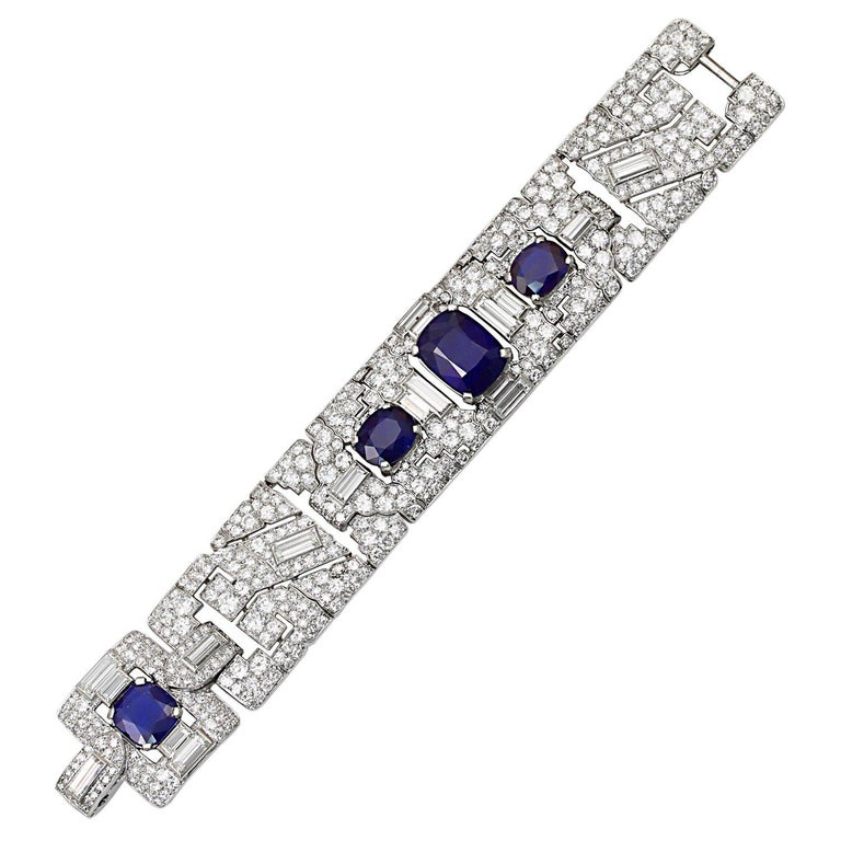 A magnificent and extremely rare art deco bracelet by Cartier, designed with a broad geometric design centering upon a large natural, no heat cushion shape sapphire accented by baguettes and old-mine diamonds extending towards two small oval shape