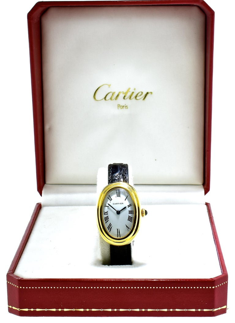Cartier Baignoire 18K vintage 18K yellow gold wristwatch with reference no. 780941795,. the dimensions are: 23x32mm, this fine watch is a manual wind movement, with a white dial and the black hands are Roman numerals.  The Cartier strap has slight