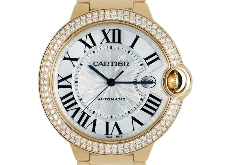 A 42mm Ballon Bleu in yellow gold by Cartier. Featuring a silver dial with a guilloche centre concealed by sapphire crystal, complimented by Roman numerals, sword-shaped hands in blued steel and a secret Cartier signature at V of VII. The guarded