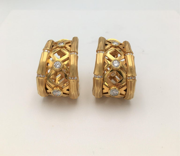 Authentic Cartier 'Bamboo' hoop earrings feature bezel set high-quality round brilliant diamonds weighing an estimated 1.45 carats total. Crafted in 18 karat yellow brushed gold the bamboo links are connected by rows of smaller round brilliant cut