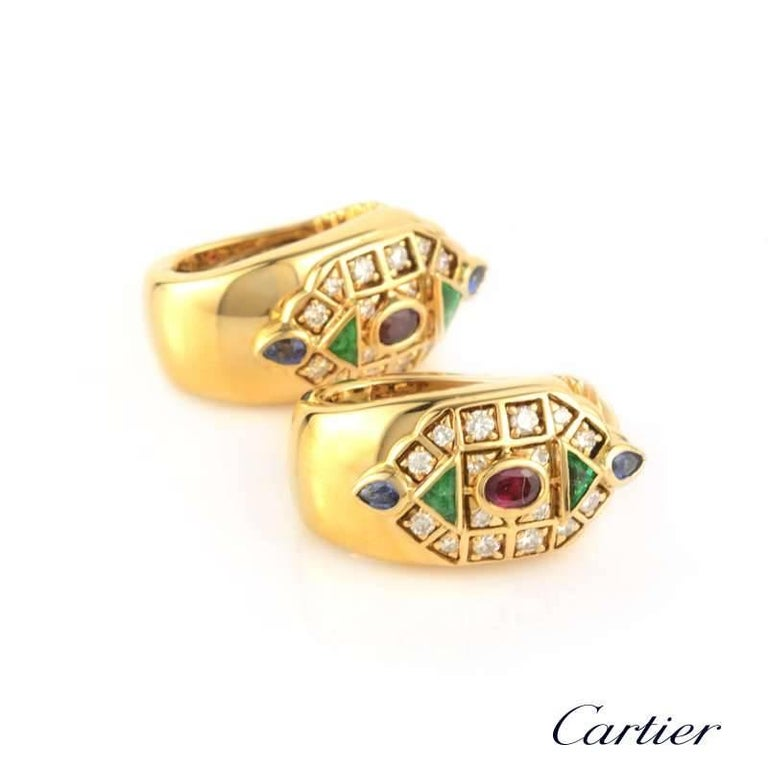 A pair of multi stone ear clips from the Cartier Byzantine collection. The front of the ear clip is set with a geometric mosaic of round brilliant cut diamonds, triangular emeralds, pear shape sapphires and oval rubies. Signed Cartier with the