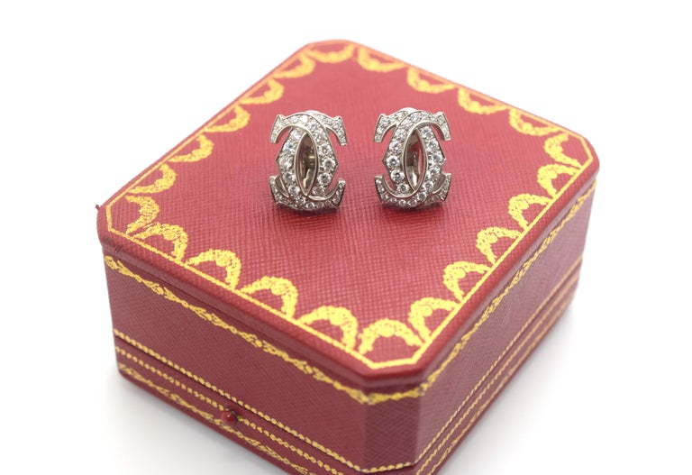 A pair of 18k white gold Cartier earrings from the C de Cartier collection. Each earring is composed of the iconic C de Cartier, interweaving C motifs with 34 graduated round brilliant cut diamonds with a total of approximately 1.66ct, G colour and