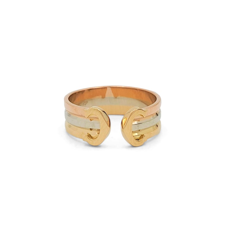 Authentic Cartier 'C De Cartier' ring crafted in 18 karat rose, white and yellow gold. The open shank ring is comprised of three bands of gold, each a new color. Cartier's trademark 'C' shape is featured at each end of the split facing inward. The