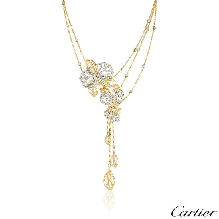 A rare 18k yellow and white gold necklace and ring suite from the Caresse d'Orchidees collection by Cartier. The ring and necklace are of openwork design and feature round brilliant cut diamonds. The ring has a total of approximately 1.60ct and the