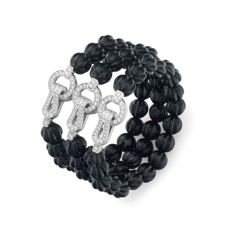 A magnificent bracelet by Cartier designed as three rows of carved onyx beads, joined by three round brilliant cut diamond stylized buckle hook clasps. The bracelet has french hallmarks, Cartier signature, and Cartier serial number.  Cartier Retail
