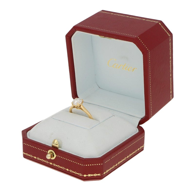An extremely elegant Cartier single solitaire engagement ring set in 18k yellow gold.   The piece prominently features a beautiful certified 1.25ct round brilliant diamond. The diamond is four claw set to centre within a v-shaped double gallery