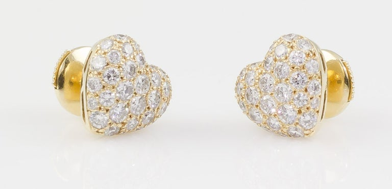 Fine 18K yellow gold and diamond heart shaped earrings by Cartier. They feature approx. 1.75-2.0cts of high quality round cut diamonds.   Hallmarks: Cartier, 750, reference numbers, maker's mark.
