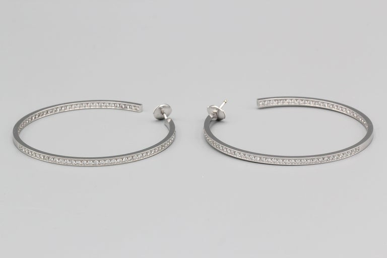 Beautiful 18K white gold and diamond hoop earrings by Cartier. They feature an