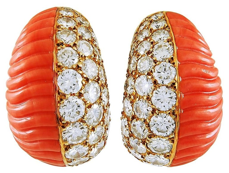 Comprised of 18k yellow gold, this pair of Cartier ear clips and matching bombe ring are finely set with brilliant-cut round diamonds adjacent to a vibrant carved coral. Signed Cartier Paris. circa the 1960s