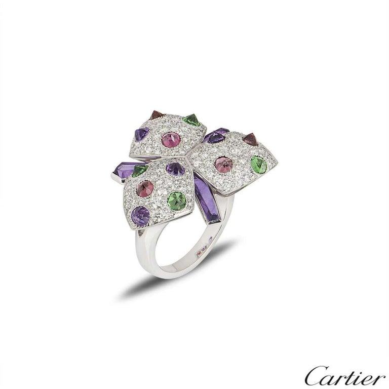 A striking dress ring from the Caresse d'Orchidées collection by Cartier. The ring features pave diamonds and reverse set amethysts, pink tourmalines and tsavorites. The diamonds have a total weight of approximately 0.40ct and the gemstones have an