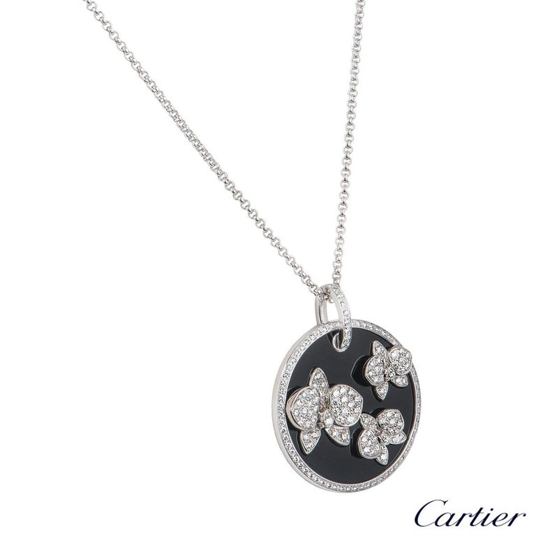 A beautiful 18k white gold diamond and onyx pendant by Cartier from the Caresse D'Orchidees collection. The pendant comprises of a circular onyx motif with 3 orchid motifs pave set with round brilliant cut diamonds. The pendant has 146 round