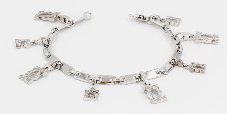 Fine diamond and 18K white gold charm bracelet by Cartier. It features a link bracelet adorned with 8 Cartier double