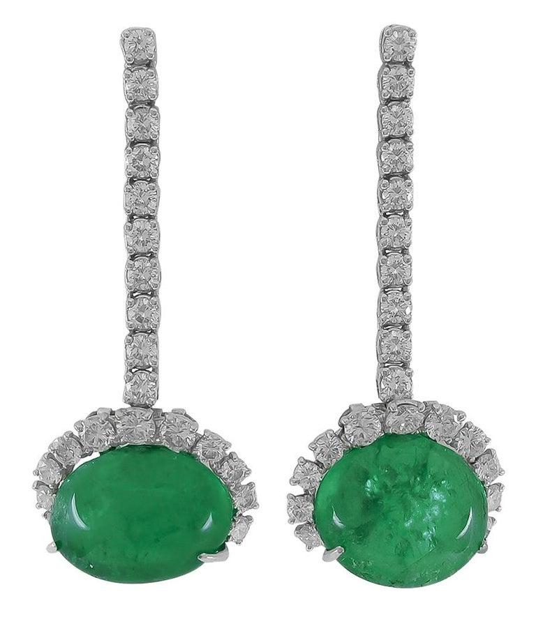 An exceptional suite by Cartier that dates back to the 1960s, comprising a necklace, bracelet, and matching ear clips, all of a similar design. Each piece is crafted with cabochon rubies and cabochon emeralds, further accentuated with brilliant