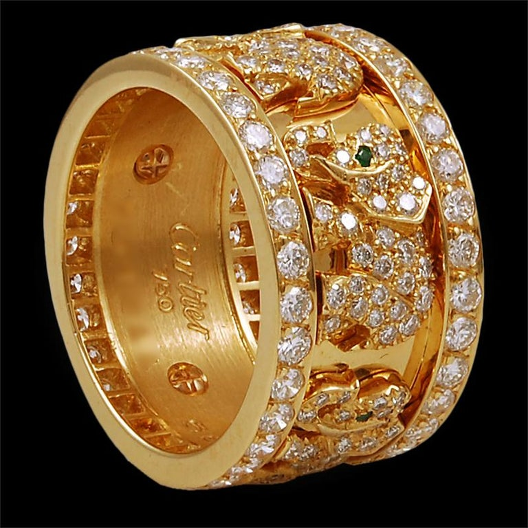 A sublime and charming wide band-ring by Cartier featuring a line of elephants between a border of round cut diamonds above and below. Each elephant is exquisitely pavè set with brilliant-cut diamonds, their eyes accentuated with a vibrant