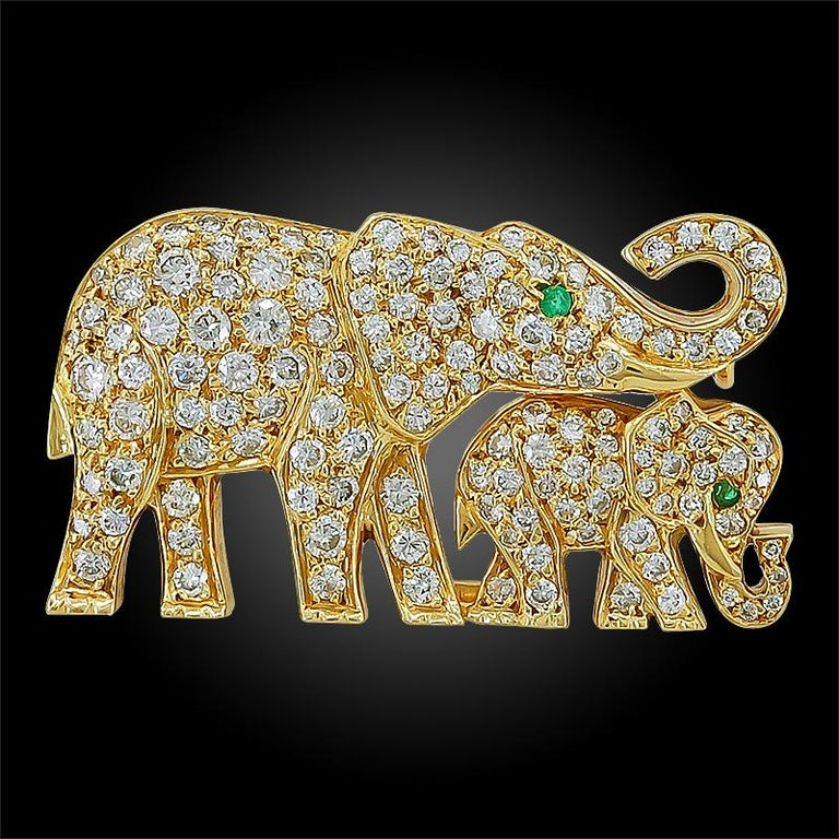 A charming brooch by Cartier designed as a mother and baby elephant, each comprised of 18k yellow gold, entirely pave set with round brilliant-cut diamonds. Each elephant head is adorned with a round cut emerald eye, signed Cartier,