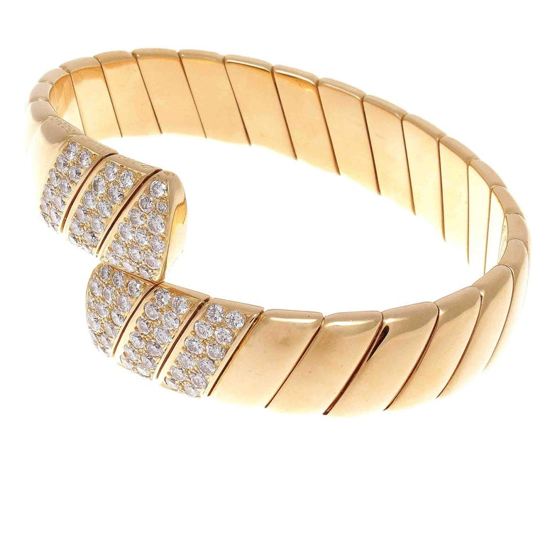 Cartier's undeniable style has reigned supreme for multiple centuries. Featuring flowing sections of glistening 18k yellow gold ending in radiating sections of brilliant white diamonds that are D-E color, VVS clarity. Signed Cartier, numbered and
