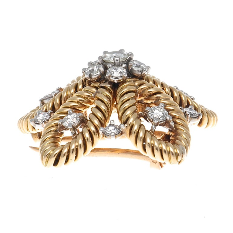 Classic Cartier fashion that benefits the jewelry world. An astute accessory that can be worn by anyone. Featuring an everlasting blooming flower of diamonds and gold that is perfectly assembled. Signed Cartier Paris and numbered.
