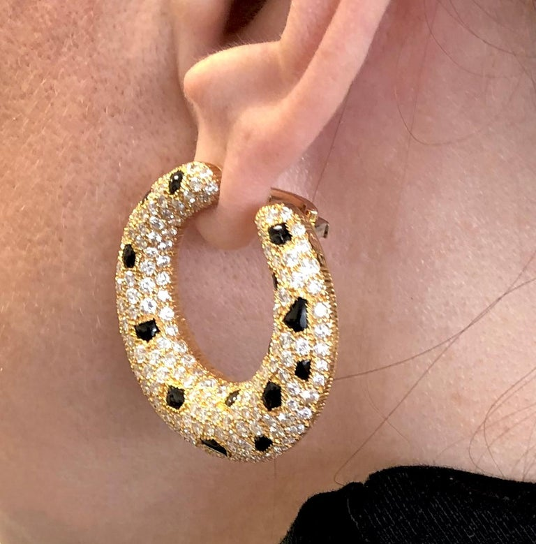 CARTIER Panthere Vintage Diamond Hoop Earrings in 18k Yellow Gold. A vintage Cartier de Panthère design, with white round brilliant pavé set with custom-cut onyx cabochons in textured gold frames. The hoops feature an asymmetrical post to give the