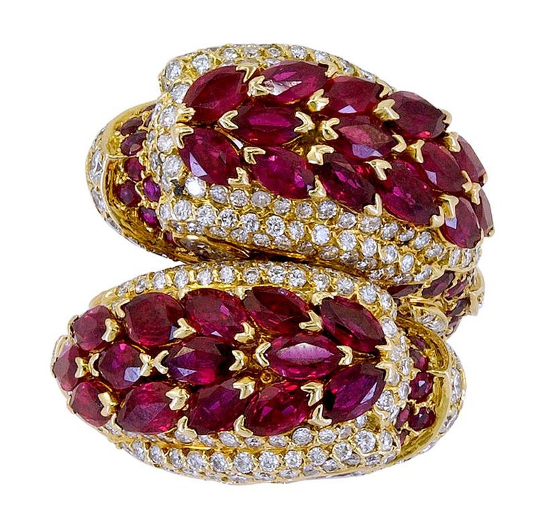 """CARTIER Diamond, Ruby Dolphin Ring.  An 18k yellow gold design as two heads dolphin ring, set with rubies and round diamonds. Signed """"Cartier"""" and numbered, with French assay, circa 1975 ring size - 5.75"""