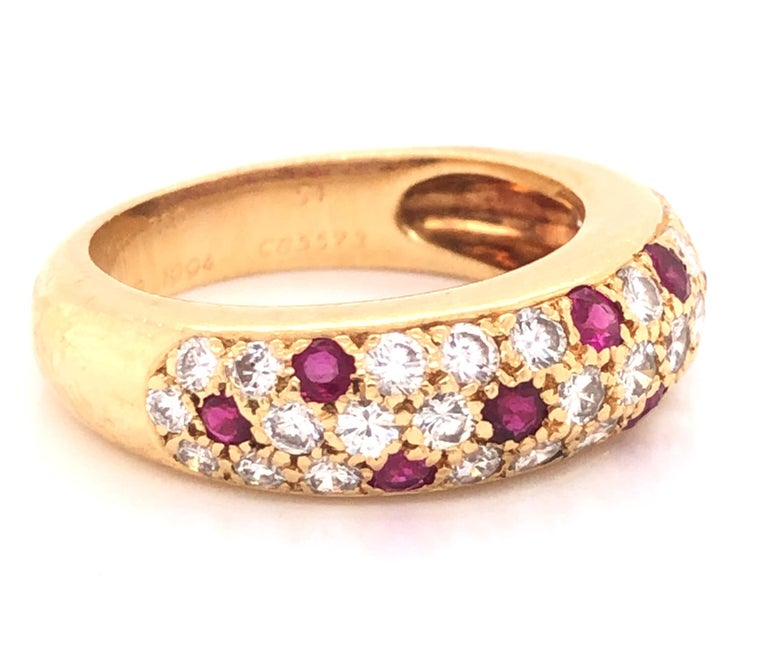 Beautiful design from famed jewelry house Cartier. This ring is crafted in 18k yellow gold, from the Mimi collection. Ring features approximately 1.00 tcw. of G/VS diamonds and rubies. The diamond and rubies set against the yellow gold truly pop off