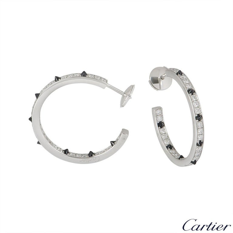An 18k white gold pair of diamond and onyx earrings by Cartier from the Panthere De Cartier collection. The earrings are set with pave round brilliant cut diamonds and onyx spikes on either side of the hoops. The 52 diamonds have an approximate